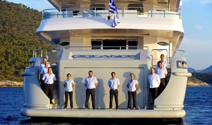 the entire crew of megayacht O'ceanos on the aft deck posing