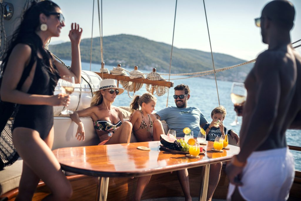 a relaxed family scene on the deck of a motor sailer on vacation
