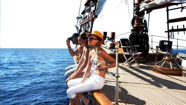 yacht charter clients dangling legs over the yacht side