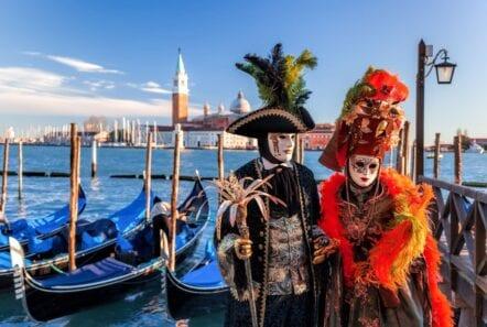 festival of Venice two masked goers near gondolas